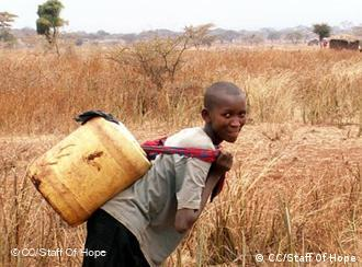 A girl carrying a plastic water can on her back