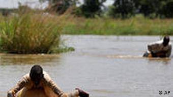 Local residents use calabash gourds as flotation devices as they swim across flooded farmland in Gudinchin village, near Dutse in northern Nigeria, Monday, Sept. 27, 2010. (AP Photo/Sunday Alamba)