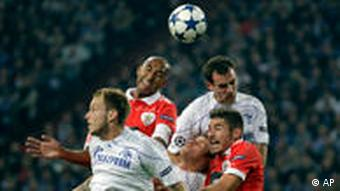 Lisbon's Luisao, rear left, anmd Schalke's Christoph Metzelder, rear right, challenge for the ball during the Champions League Group B soccer match between FC Schalke 04 and SL Benfica Lisbon, in Gelsenkirchen, Germany, Wednesday, Sept. 29, 2010.