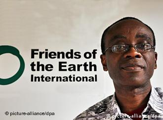 Nigerian activist Nnimmo Bassey in front of sign for Friends of the Earth international