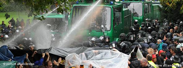 Police spray demonstrators with water cannon