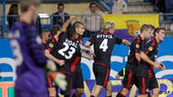 Bayer 04 Leverkusen's Eren Derdiyok, fourth from the left, celebrates his goal with teammates during a Europa League soccer match against Atletico Madrid at the Vicente Calderon stadium in Madrid Thursday Sept. 30, 2010.