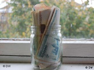 Белорусские рубли, помещенные в банку, стоят на подоконнике