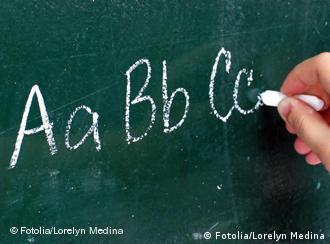 A hand writes letters on a chalkboard
