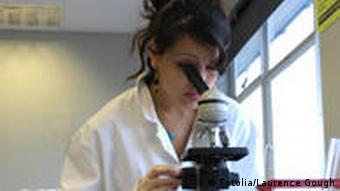 A school girl looks through microscope