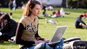 A woman typing on a laptop in a park