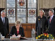 默克尔在不来梅市政厅留言,站着的是伍尔夫夫妇和不来梅市长博伦森