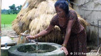 Sheni Chaudary pumps water from a well at her house in Badreni Village