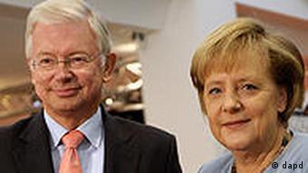 Hessens ehemaliger Ministerpräsident Roland Koch und Bundeskanzlerin Angela Merkel posieren am 04.10.2010 in Berlin zu Beginn der Vorstellung von Kochs Buch Konservativ (Foto: dapd)