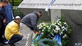 Unidentified members of the Israeli athletics federation place flowers in front of the monument, during a memorial ceremony near the Olympic Village in Munich, Sunday, Aug. 11, 2002. On Sept. 5, 1972, Palestinian terrorists stormed an Olympic Village apartment house at the Munich games, killing two Israeli athletes and holding the others hostage in an effort to gain the freedom of 200 Palestinian prisoners held by Israel. In a botched rescue attempt after a 20-hour standoff, nine more Israeli athletes were killed, as well as five terrorists and a German policeman.
