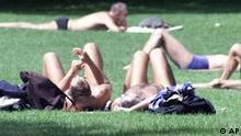 Berliner geniessen die Sonne auf einer Liegewiese im Tiergarten