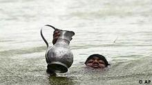 A Bangladeshi boy swims through flood waters carrying drinking water, in the Mohammadpur area in the outskirts of Dhaka, Bangladesh, Sunday, Aug. 11, 2002. The monsoon floods have left at least 141 dead in Bangladesh as flood waters submerged nearly half the country, leaving more than 6 million people stranded.