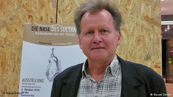 Der Kölner Karikaturist Burkhard Fritsche vor einem Ausstellungsplakat