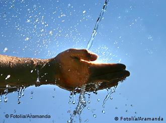 A stream of water flows into a person's cupped hand
