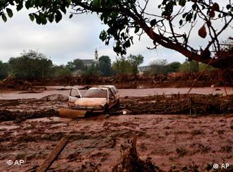 A wrecked car, washed away by a flood of toxic mud, stands in a field in the village of Kolontar