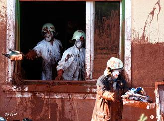 Katastrophenschutzmänner helfen bei der Beseitigung des sChlamms (Foto: AP)