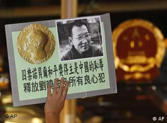Pro-democracy protesters hold the picture of Chinese dissident Liu Xiaobo with Chinese words reading: 'Nobel Peace prize winner held in Jail is China's shame