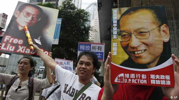 Pro-democracy protesters in Hong Kong hold the picture of Chinese dissident Liu Xiaobo demanding his release