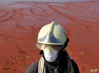 A Hungarian firefighter stands guard at the red sludge