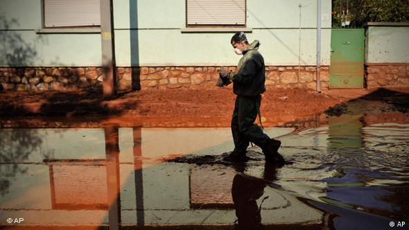 A Hungarian firefighter wearing protective gear walks in a street flooded by toxic red sludge in Devecser, Hungary, Saturday, Oct. 9, 2010. The population of the neighboring town of Kolontar was evacuated early this morning, and Devecser with a population of 5,300 is also in the likely path of a new sludge deluge. Authorities asked residents to put their most essential belongings into a single bag and prepare for possible evacuation. (AP Photo/Bela Szandelszky)