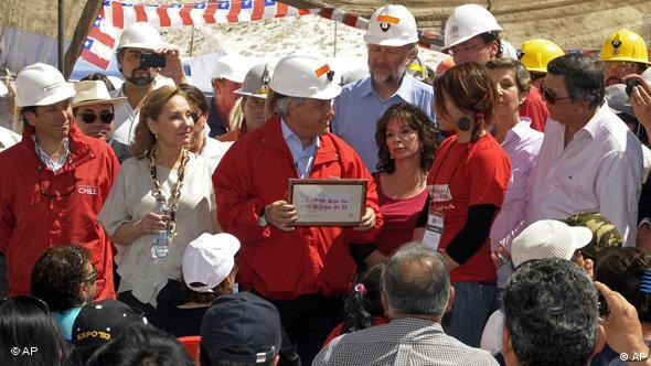 Президент Чили Себастьян Пиньера держит в руках сообщение от шахтеров: Мы живы, все 33 человека