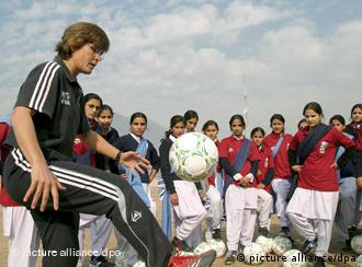 German soccer coach Monika Staab, left, gives instructions to Pakistani women soccer players