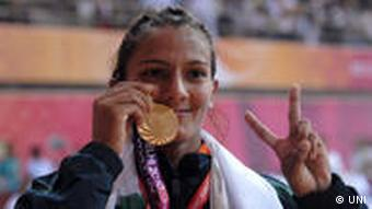 Geeta displaying her gold medal in the 55 kg category women's wrestling contest