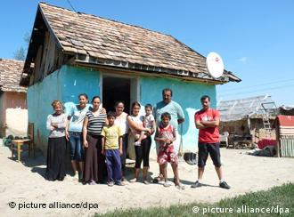 A Roma family in front of their house in Romania