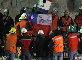 Rescued miner Jose Ojeda holds up a Chilean flag