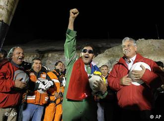 The last miner to be rescued, Luis Urzua, center, gestures as Chile's President Sebastian Pinera, right, looks on after his rescue from the collapsed San Jose gold and copper mine