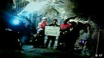 In this screen grab taken from video, rescuers inside the San Jose Mine near Copiapo, Chile, hold a sign that reads Mission Complete in Spanish after all 33 trapped miners were rescued Wednesday, Oct. 13, 2010. (AP Photo)