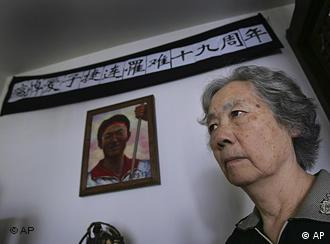 FILE - In this Juen 4, 2008 file photo, Ding Zilin, co-founder of the Tiananmen Mothers, a group representing families of those who died in the 1989 crackdown on pro-democracy demonstrations, stands in front of a shrine to her son, Jiang Jielian, who died at 17, at her apartment in Beijing, marking the 19th anniversary of the military assault in Tiananmen Square. In the week after Liu Xiaobo won for his decades of promoting democratic change in China, dozens of people who openly agreed with his views say they have been detained, roughed up, harassed or kept from leaving their homes. The latest appears to be a woman who Liu has said should win the prize: Ding Zilin, who has fought for years for China's government to recognize the hundreds killed in the military's crackdown. Liu's wife sent out an alert late Thursday, Oct. 14, 2010, that said Ding had disappeared and urged people to pay attention to her case. (AP Photo/Greg Baker, File)