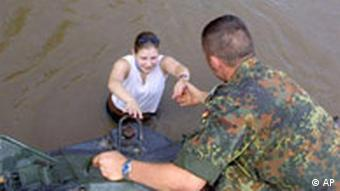 A Bundeswehr soldier helps a woman out of water in a flood