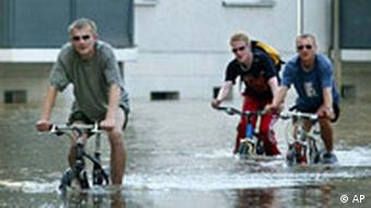 People bike in a flooded street in a district of the eastern German city of Dresden on Friday evening, Aug. 16, 2002