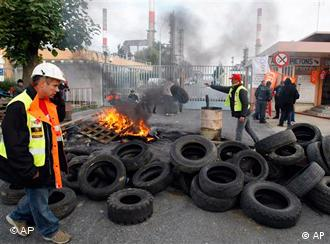 Striking workers next to a blackade of tires in front of a refinery