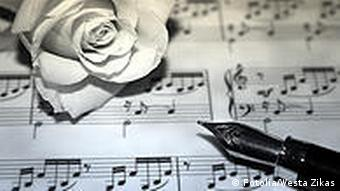 White rose and fountain pen on sheet music