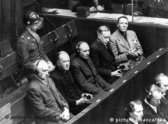 Some of the accused at the Nuremberg Trials on December 6, 1945 - from left to right: Karl Doenitz, Hermann Goering and Rudolf Hess - watched over by two American soldiers