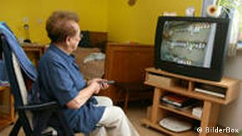 Old woman sitting in front of the television