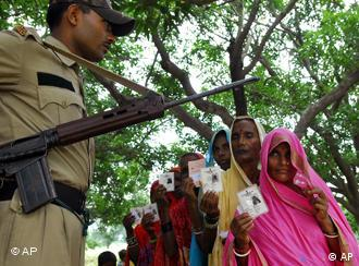 A security officer stands guard, as voters display their election identity cards in the state of Bihar state