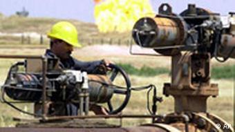 Iraqi oil worker checks equipment at Kirkuk oil refinary, Iraq
