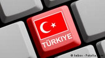 A grey computer keyboard with a red key with the Turkish flag on it