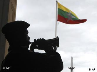 Member of the Guard of Honor blows a horn with the Myanmar flag in the background