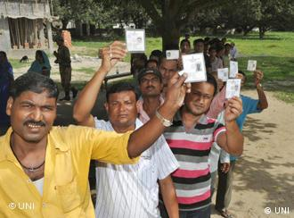 KISHANGANJ, OCT 21(UNI):- -Voters showing their electoral identity cards while queuing up to cast their votes inthe campus of Madarsa Anjuman Islamia in Kishanganj during first phase of Bihar Assembly Election on Thursday. UNI PHOTO -55U