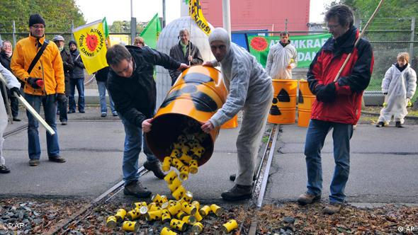 Protestors empty a barrel of cans onto railroad tracks. The cans are painted with radioactivity symbols.