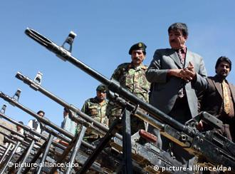 Afghan security officials inspect weapons collected from certain private security firms