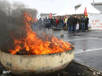 Striking workers block the main entrance of the an oil depot, protected by riot police officers, at Fos sur Mer