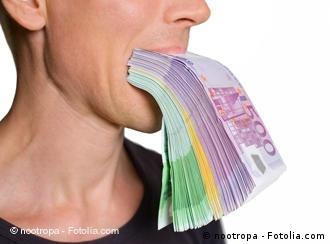 Person biting on a pack of euro currency notes