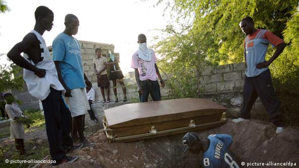 Haitians assist in the burial of Tikont Dolamard, one of the victims of cholera