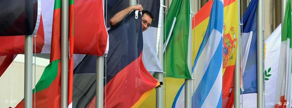 A man adjusts the German flag between the flags of the EU member states in front of the Congress Center in Prague, Czech Republic, on Saturday, April 4, 2009, which will hosts the upcoming EU-USA Summit. US president Barack Obama is scheduled to arrive in the Czech Republic later on Saturday. He will attend a summit between the United States and the 27-member European Union in Prague on Sunday April 5, 2009. (AP Photo/Bela Szandelszky)