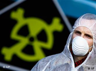 A man in a hazmat suit in front of a radioactivity sign